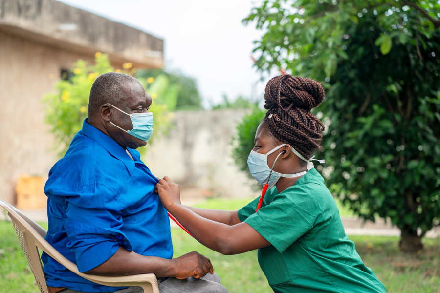 image of an aged African man being checking up by a health worker-young black nurse wearing a face mask taking care of an old man- health wo.jpg
