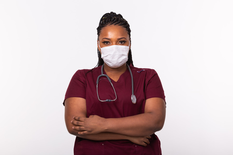 African american doctor in a medical mask over white background. Medicine, healthcare and people concept..jpg