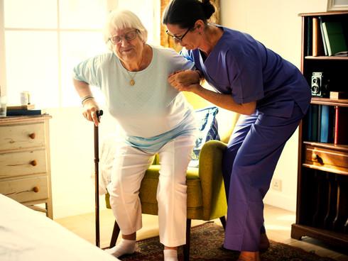 Nurse helping senior woman to stand up.j