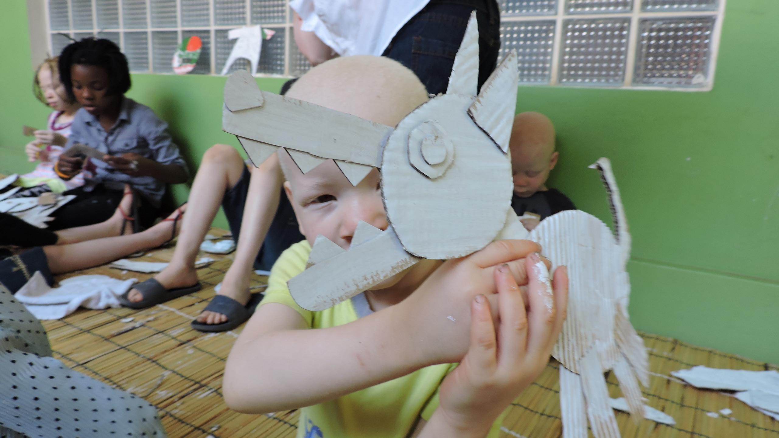Carita de niño albino tras el cartón