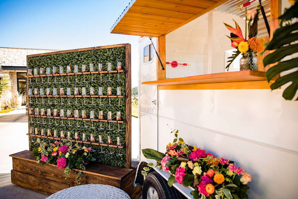 Champagne wall with cupcake trailer decorated with tropical flowers.