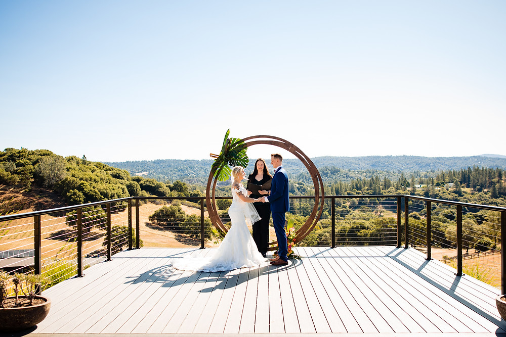 Couple standing on a deck saying their vows in front of a circular arch