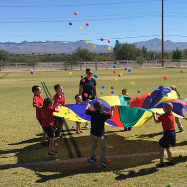students-playing-outside-with-parachute-