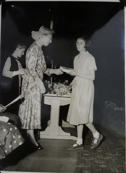 """Shirley Read-Jahn (Bailey 1954-61): """"Our school prize-giving ceremony was held in """"The Dome"""" adjacent to the Royal Pavilion in Brighton, the fantastical minaret-topped building originally intended as a stable block commissioned by the Prince Regent in 1805. I received a prize that year. My prize makes me smile now because it says it was for """"Craft"""" but I well knew it was actually for being the best basket-weaver in the school. I have always associated this work with, shall we say """"Occupational Therapy"""", so I felt a certain chagrin that I was getting that sort of a prize instead of a prize for, say, Latin! When receiving a book as my prize, the photo shows me looking away from H.R.H. the Princess Royal, the presenter of all the prizes on that occasion, and looking as if I'm about to sigh. It was Charles Dickens' The Old Curiosity Shop that I was given, and I was wondering why nobody had told H.R.H. that I already owned this book! As an aside here, I'd like to point out that in the photo I am wearing Clark's sandals. By one of life's quirks, my son has married one of the Clark family's daughters!"""""""