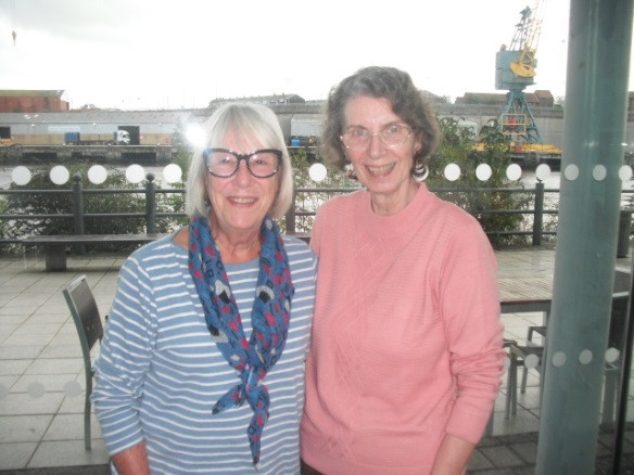 """Reunions don't come any more """"mini"""" than two Old Girls, but they are still very special and in this case very exciting for our Team Manager, Penny Harrison (Titheradge, 1969-73), since she was invited by Bridget Sudworth (Last, 1930-63) to join her and her husband for lunch while (she writes) """"they were 'up my way' on holiday in October. We met at the National Glass Centre in Sunderland and are pictured against the backdrop of the Port of Sunderland. Although Bridget is ten years my senior and we had never met we felt an instant connection."""" October 2019"""
