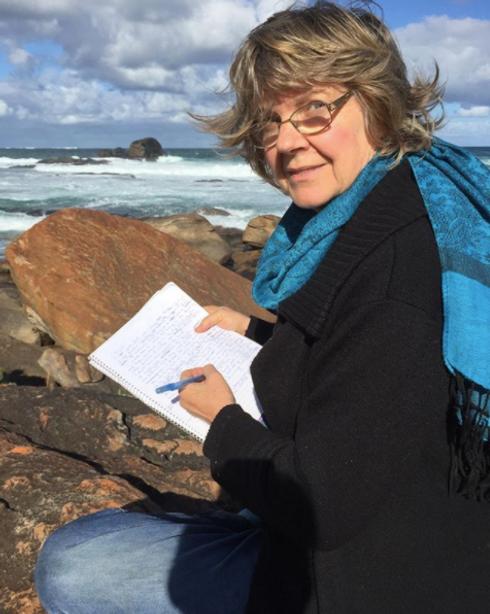 Sue writing at the beach