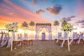beach ceremony setup with colorful sky.j