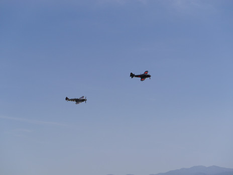空飛ぶ零戦を見て、三八式歩兵銃を持つ