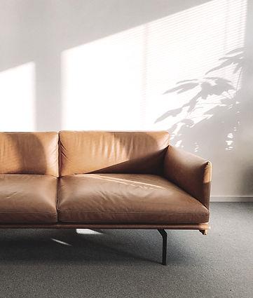 2-seat-orange-leather-sofa-beside-wall-1