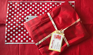 Red tissue wrapped order with gift tag a