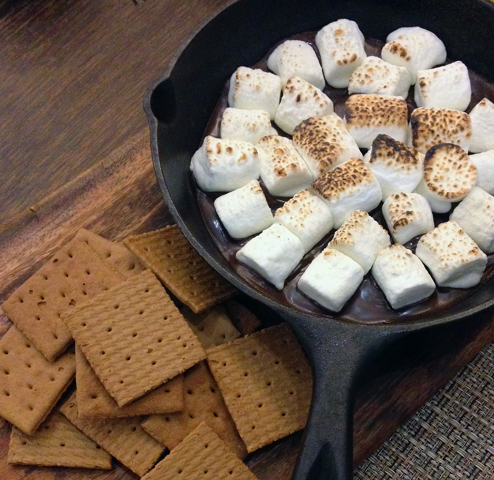 An image of toasted marshmallows on top of chocolate in a cast iron skillet with graham crackers on the side.