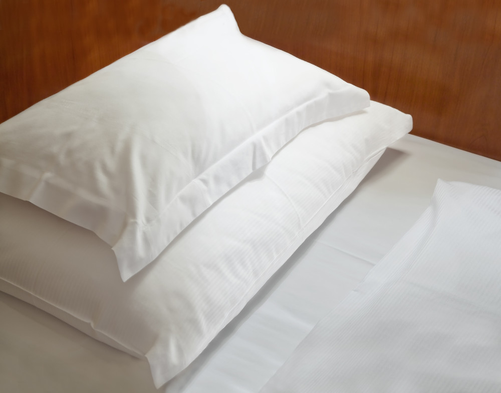 a bed with white linen and two pillows