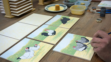 Hand painting hens on tiles