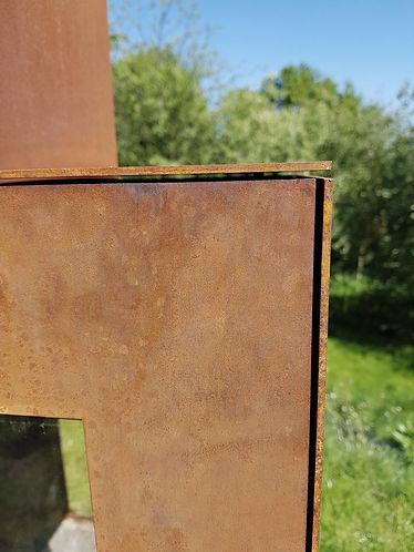 Afwerking van strakke tuinkachel in cortenstaal met 4-zijdig glas