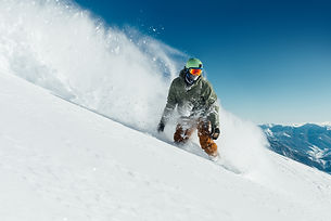 male-snowboarder-curved-and-brakes-spray