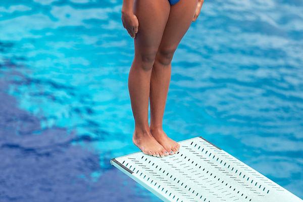 Girl standing on a springboard, preparin
