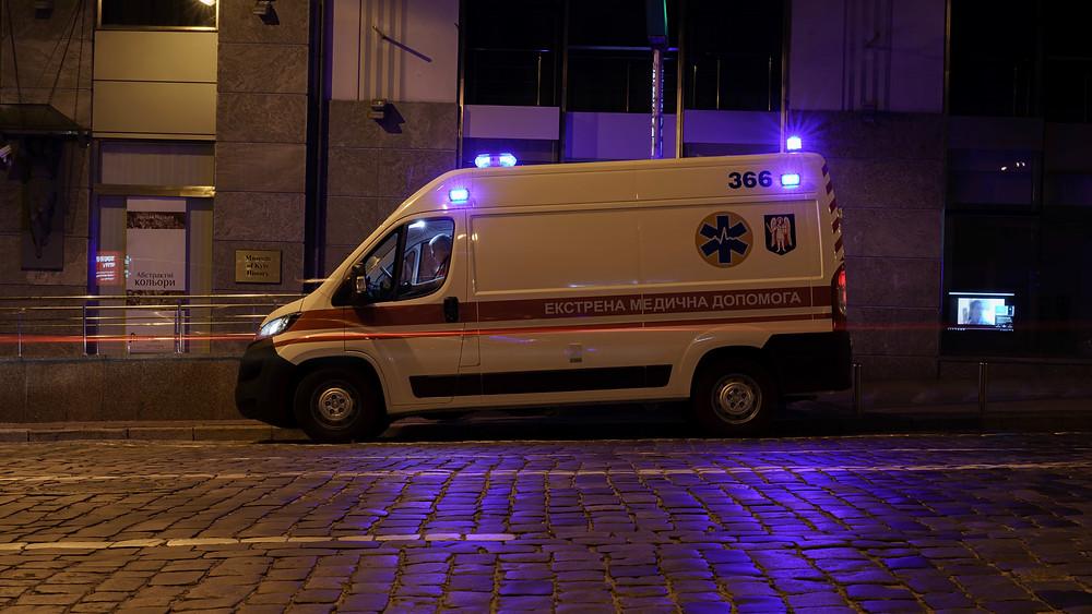 Ambulance on street at night with lights on
