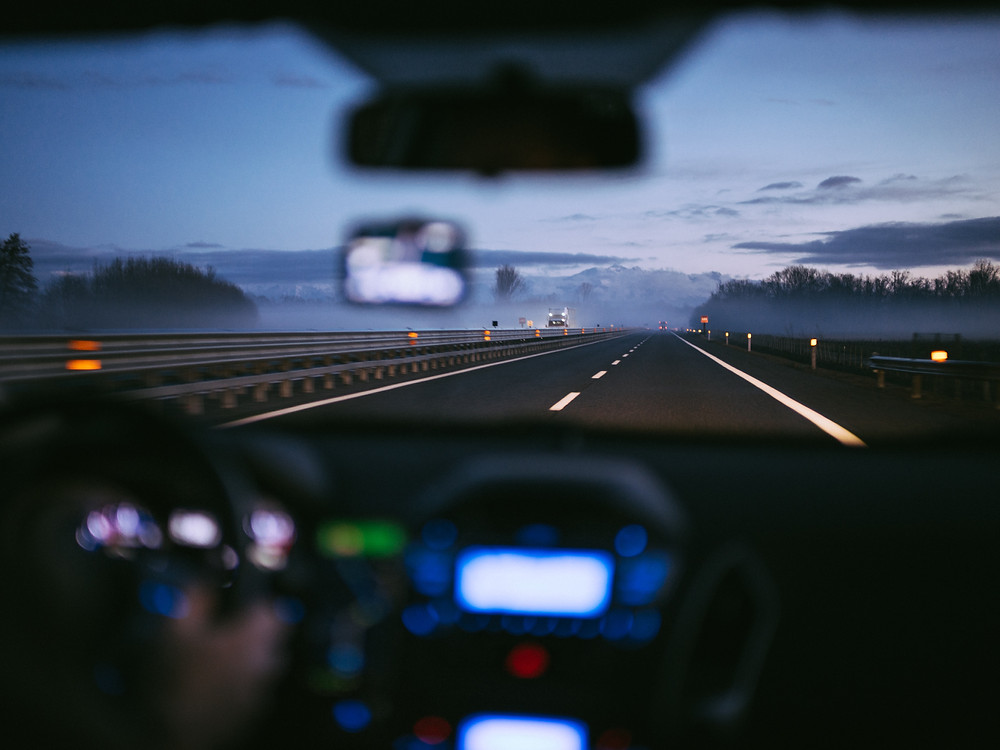 Blurry view of interior of vehicle driving down highway