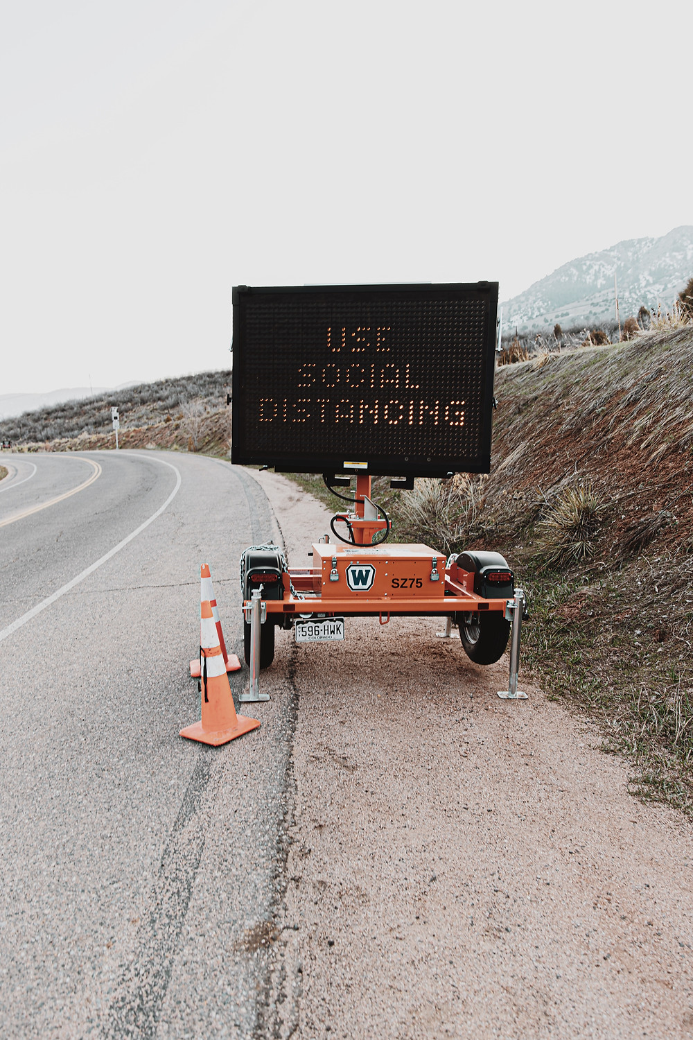 Sign on side of road reminding drivers to social distance