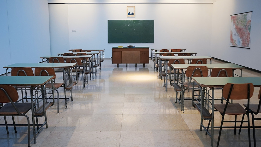 Empty classroom; desks facing chalkboard