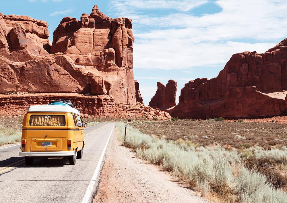 Yellow VW bus driving through desert.