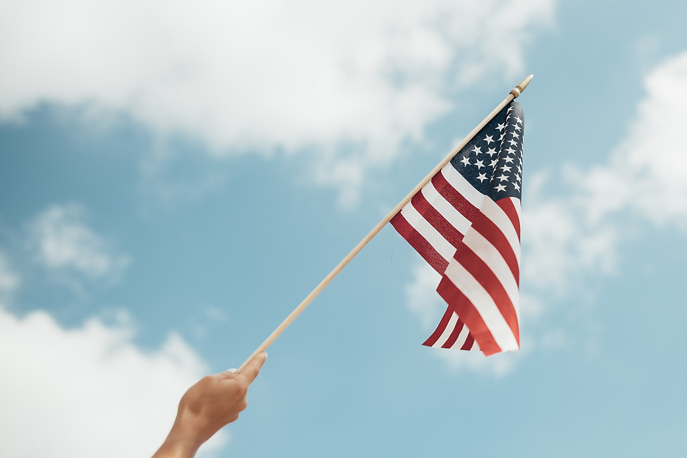 Person waving American flag against blue sky