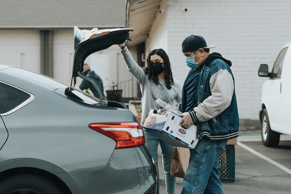 Couple putting box in car trunk.