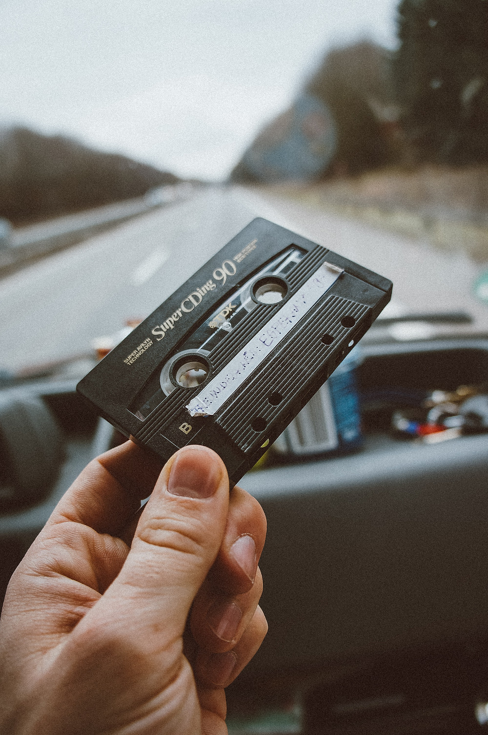 Hand holding cassette tape in vehicle