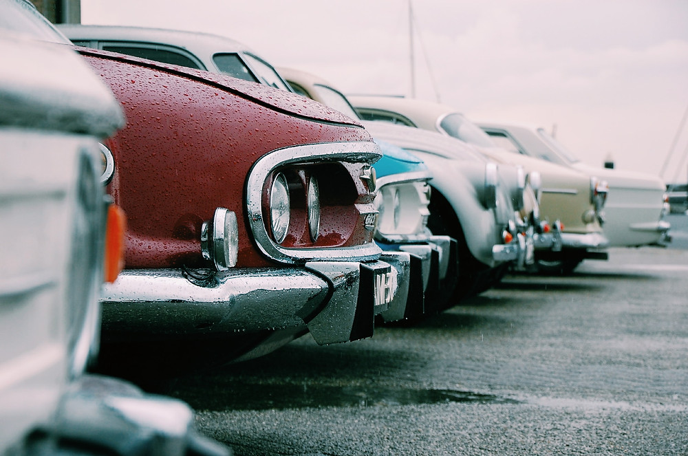 Line of old cars in a parking lot.