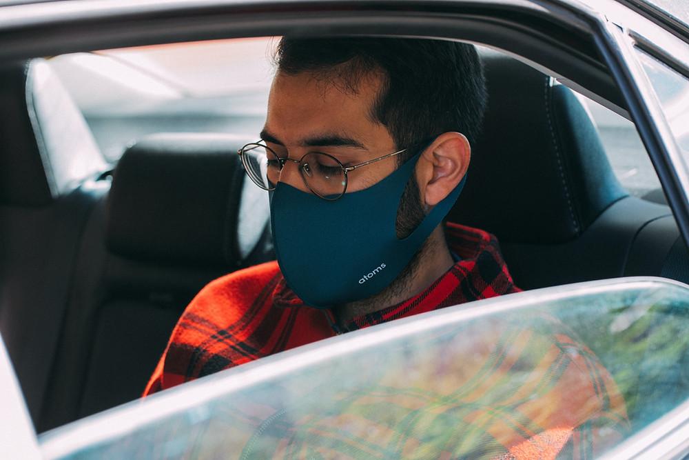 Man in car wearing face mask, window down
