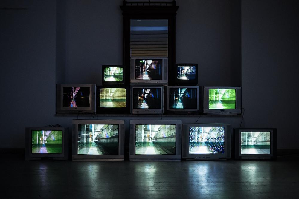 Stack of TVs in dark room.