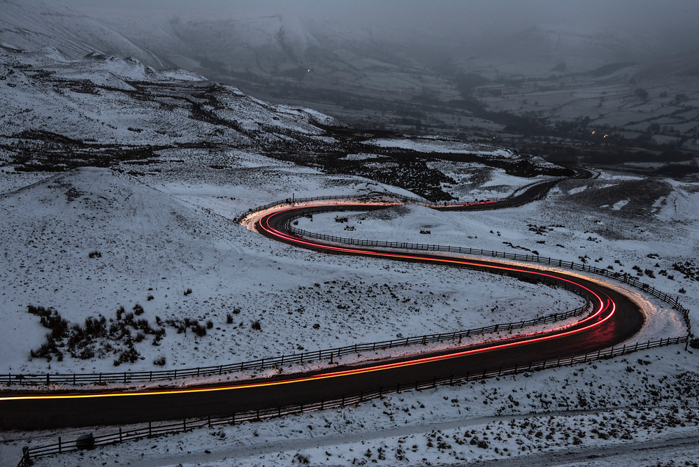 Time lapse of road winding through snowy valley