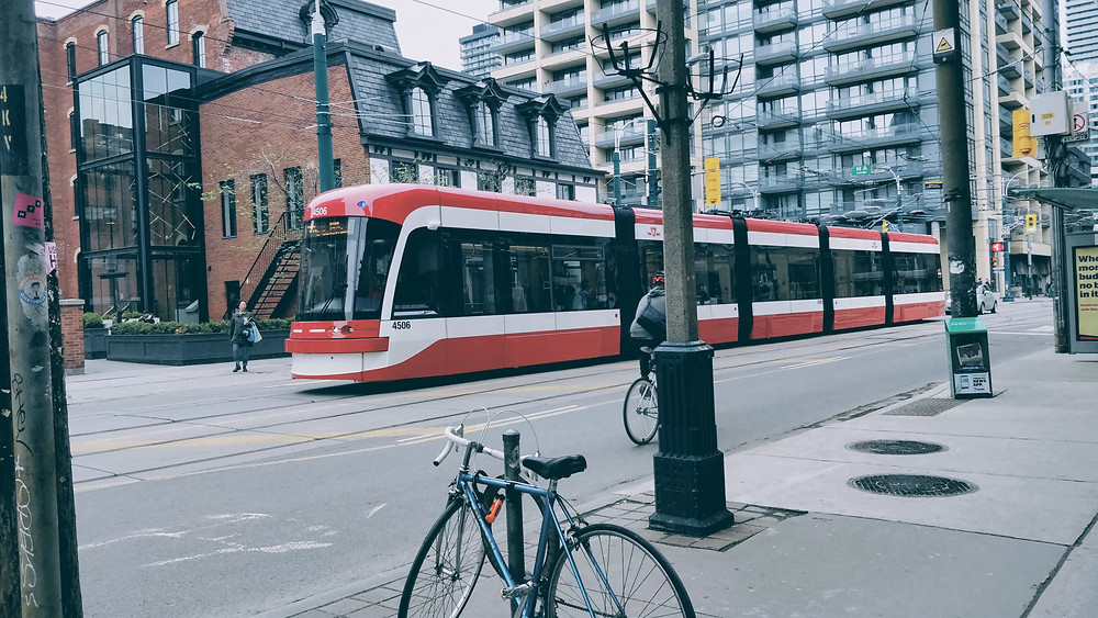 Red streetcar driving down a street in Toronto