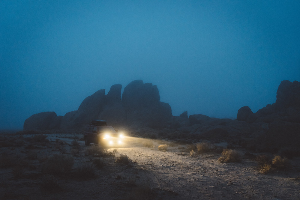 Jeep with headlights on driving at night