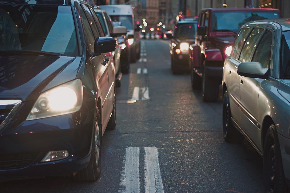 Two lanes of traffic waiting at traffic light.