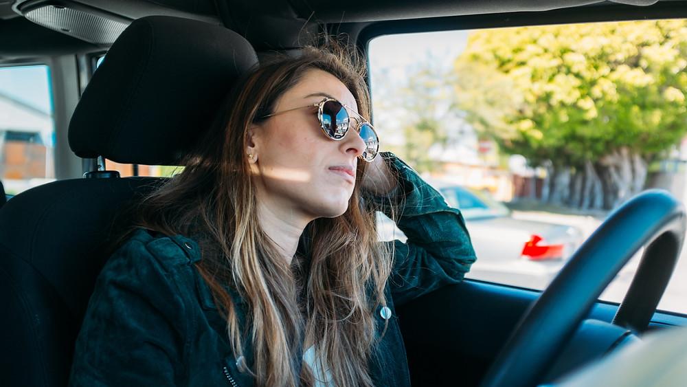 Woman sitting inside vehicle wearing sunglasses