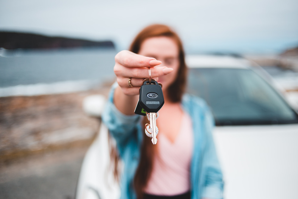 Girl holding out car keys towards camera