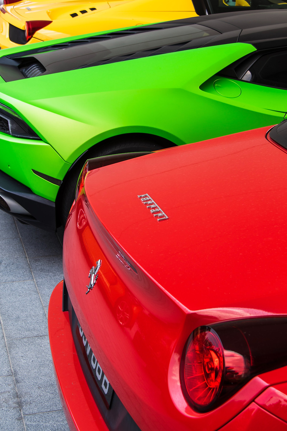 Red, green, and yellow luxury cars lined up in showroom.