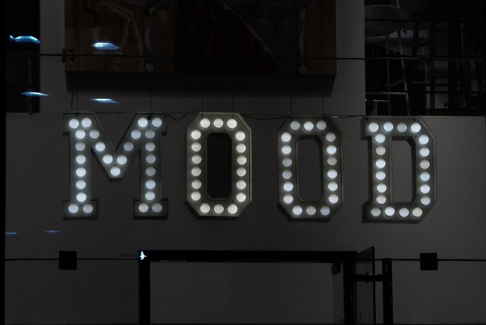 Lightbulb sign that reds 'MOOD.'
