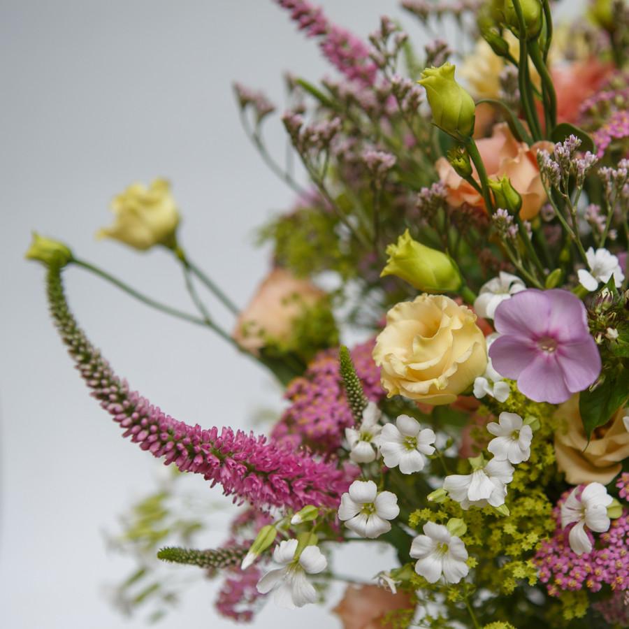 Un bouquet champêtre créer par un artisan fleuriste il est composé de véroniques, de Lisianthus,  d'œillet.