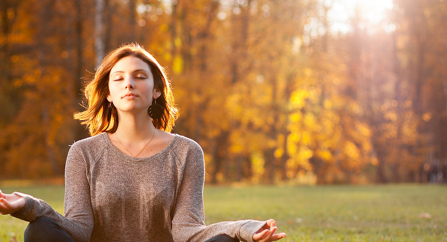 woman mediating at a park on an autumn day