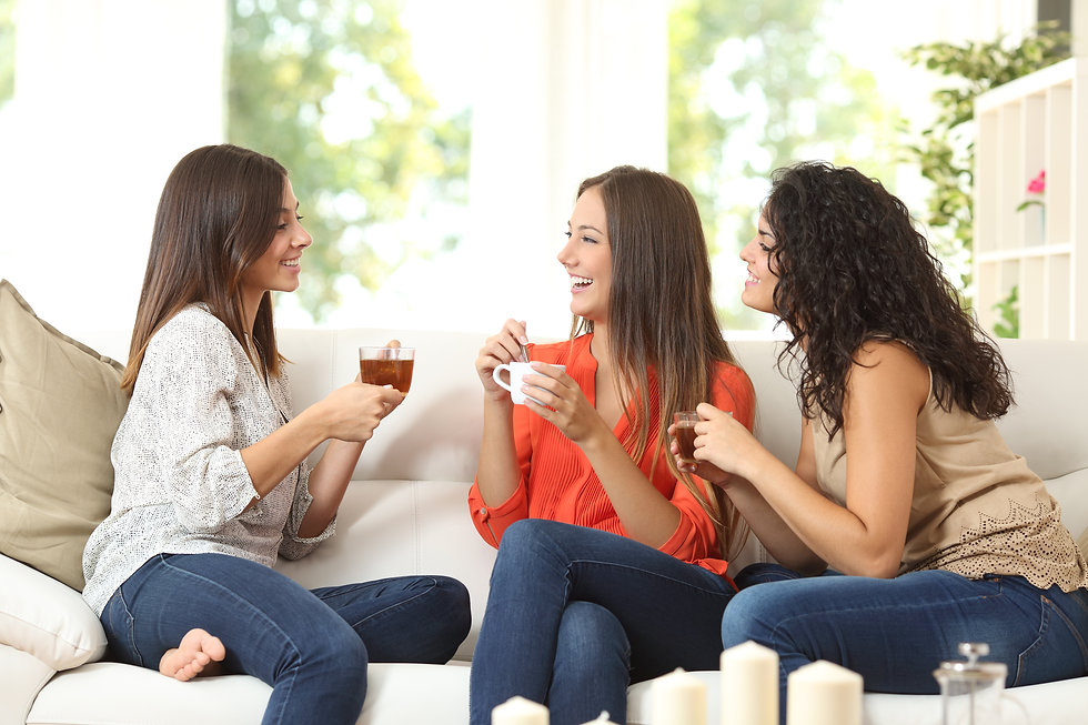 Three happy friends talking and drinking coffee and tea sitting on a couch at home.jpg