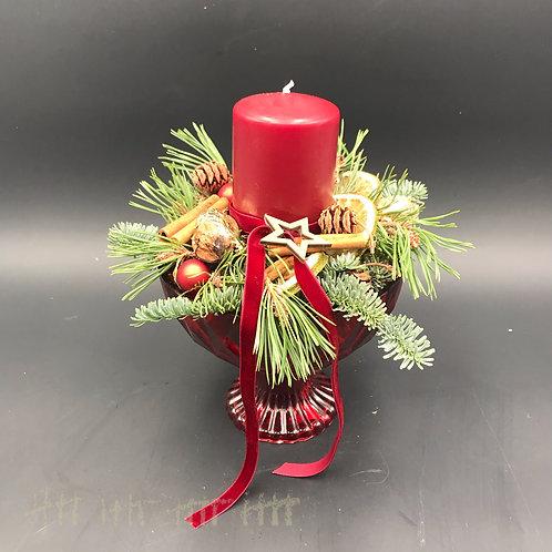 Kerzengesteck in rotem Glasgefäß