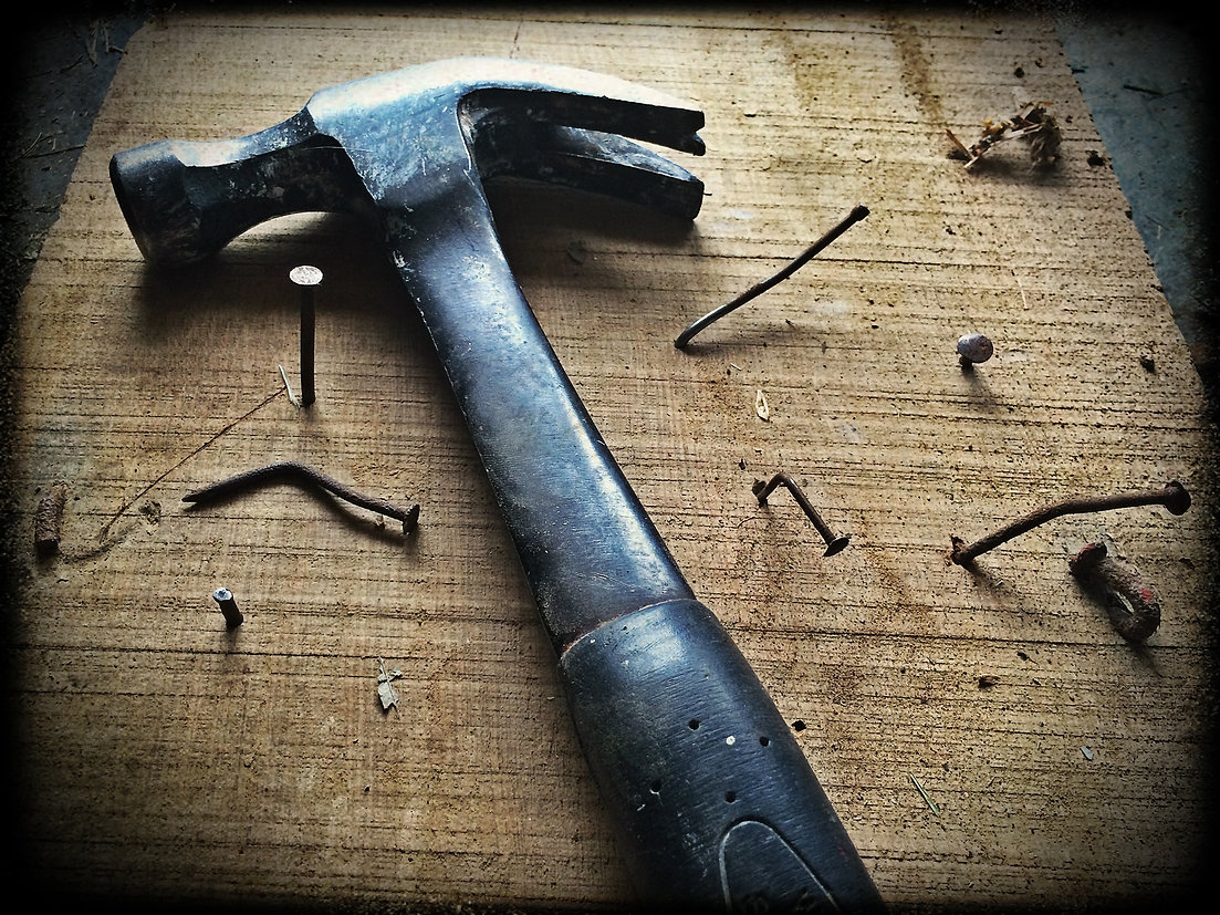 black-claw-hammer-on-brown-wooden-plank-