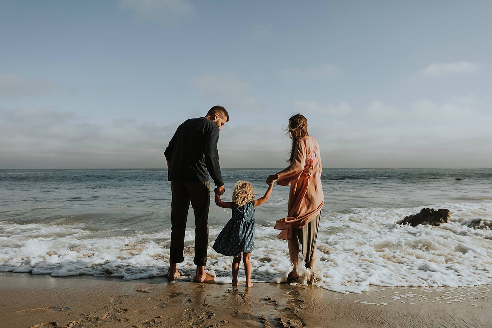Couple with your daughter walking at the beach