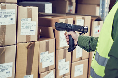 Man scanning boxes in warehouse with handheld scanner