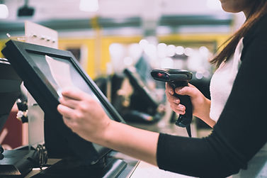 Cashier using scanner and POS system