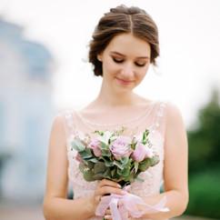 Happy young bride in a tender pink weddi