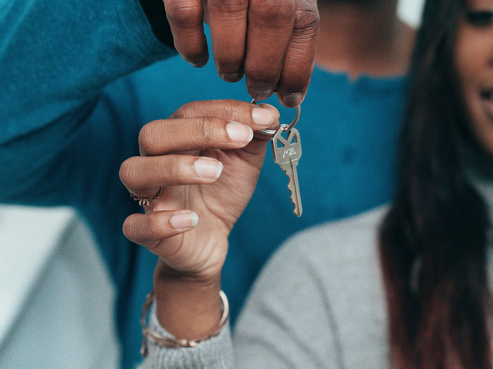 two black people's hands holding the key to their new home