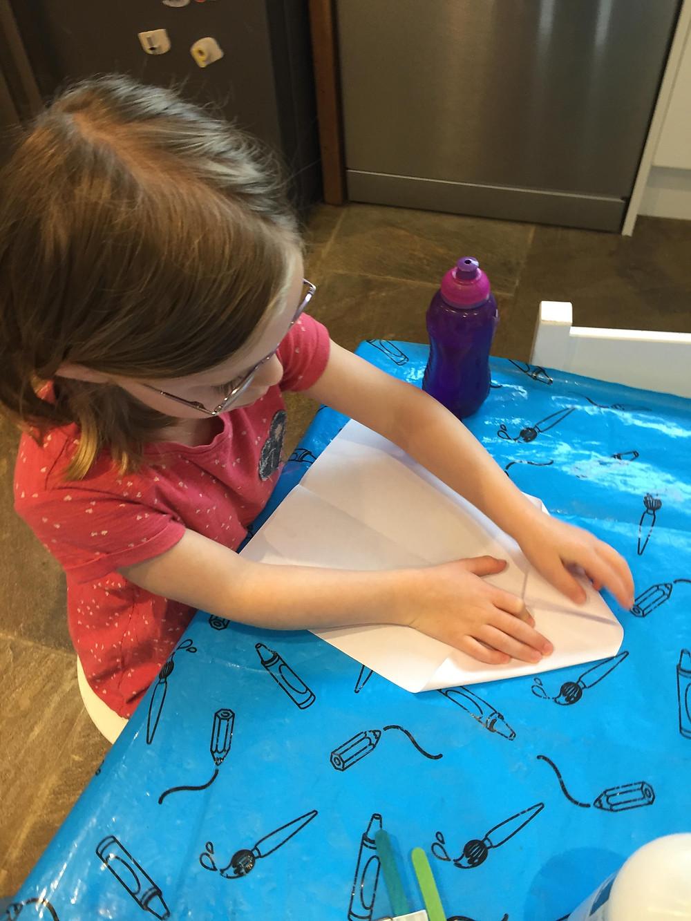 Girl folding paper plane